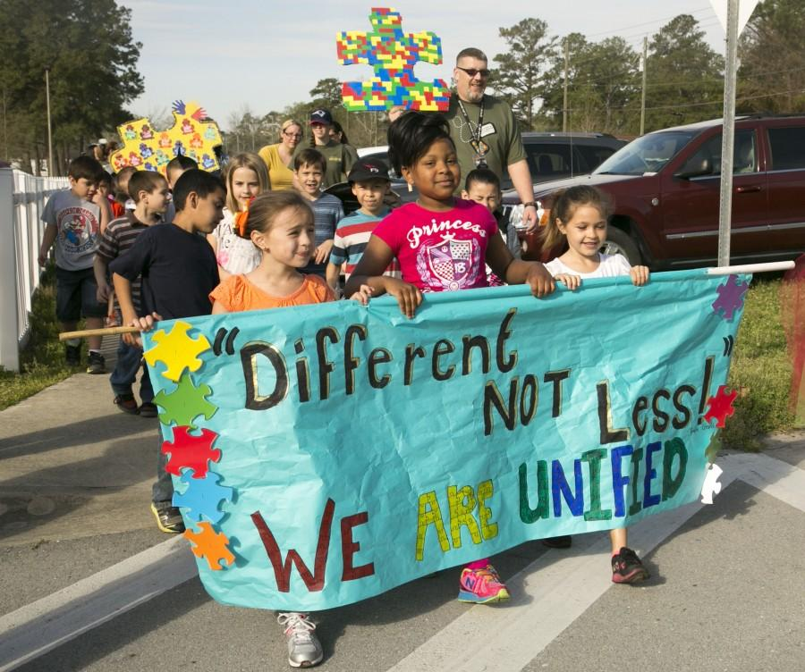 Students+and+family+members+from+Johnson+Primary+School+march%2C+holding+signs+and+banners+in+support+of+autism+awareness+aboard+Marine+Corps+Base+Camp+Lejeune%2C+Friday.+According+to+the+center+for+disease+control+and+prevention%2C+one+in+every+68+children+in+the+U.S.+is+diagnosed+with+the+disorder.+%28Photo+by%3A+Lance+Cpl.+Andrea+Ovalle%29