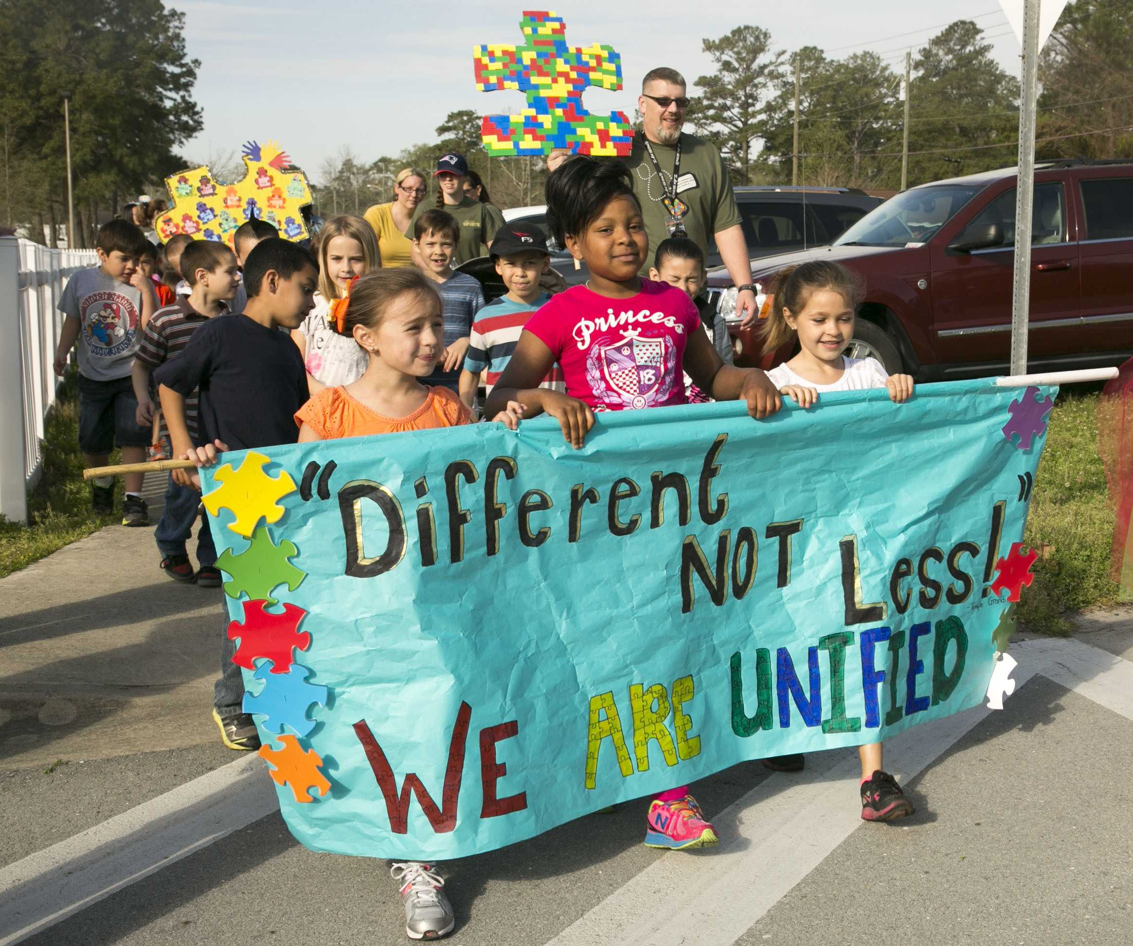 Students and family members from Johnson Primary School march, holding signs and banners in support of autism awareness aboard Marine Corps Base Camp Lejeune, Friday. According to the center for disease control and prevention, one in every 68 children in the U.S. is diagnosed with the disorder. (Photo by: Lance Cpl. Andrea Ovalle)