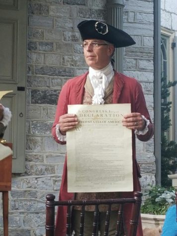 Re-enactor David Biser holds up the Declaration of Independence for the audience to see.